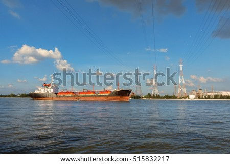 One of Power station and high voltage power lines and oil tanker at Chao Phraya river side, Bangkok, Thailand.(With warm sunlight effect in the evening )