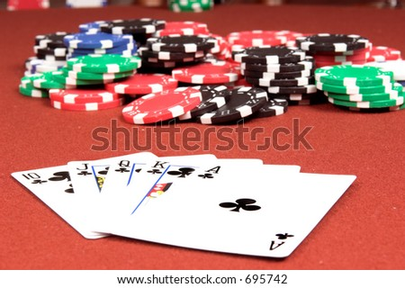 One of the highest hands in poker a Clubs Royal Flush on a red felt gaming table with a no limit jackpot in the background