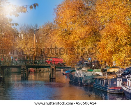 One of the numerous Amsterdam canals  in fall with bridge across water, boats along the embankment
