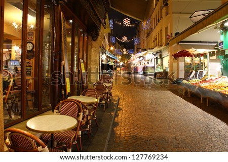 One of the oldest cobble-stoned Christmas decorated Parisian streets by late night with and fruit market and coffee house still open / Rue mouffetard by night - stock photo