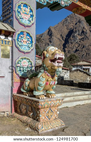 One of the two mythical beasts (left) guarding the gate of the Tengboche monastery - Nepal, Himalayas - stock photo