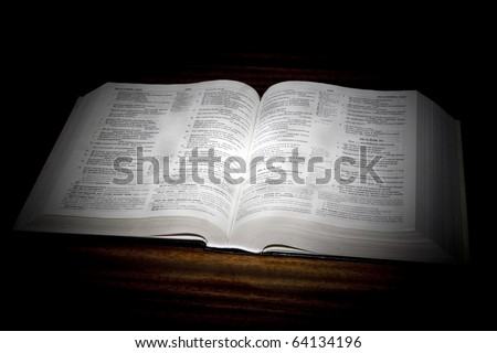 One open bible on table in black background