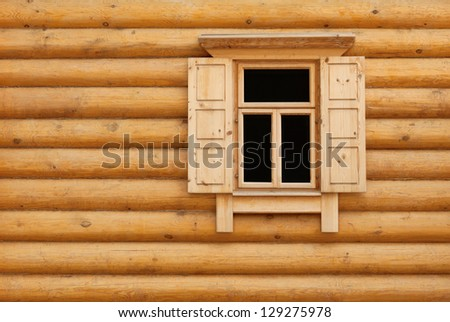 One open wooden window with shutter doors in yellow blockhouse wall - stock photo
