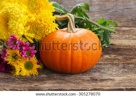 one orange pumpkin with mum flowers  on wooden textured  table  - stock photo