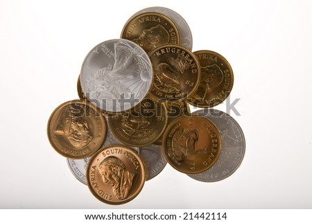One Ounce gold Krugerrand coins from South Africa and One ounce silver Walking Liberty coins from the United States of America isolated on white. - stock photo
