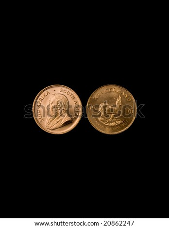 One Ounce gold Krugerrand coins from South Africa on  black background. - stock photo