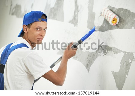 One painter with paint roller making wall prime coating  at home repair renovation work - stock photo