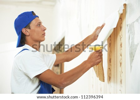 One painter worker peeling off wallpaper during interior home repair renovation work - stock photo
