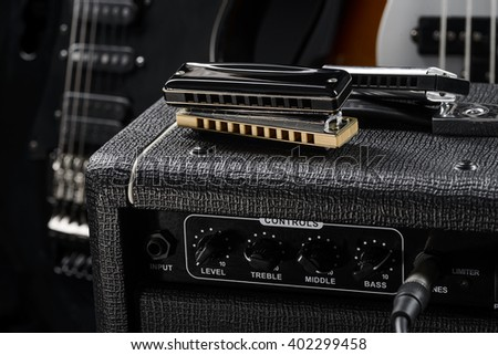One pair of blues harps is on the guitar amp. Electric black guitar is blurred in the background. - stock photo