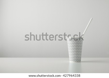 one paper cup decorated with gray black line pattern and with white drinking straw inside isolated on table Place for your text above - stock photo