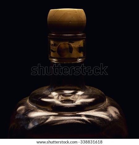 One part of an old spirit bottle, accentuated shapes with light, on black background.