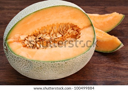 One partially cut cantaloupe, macro, with slices to the back and side on a dark wooden table.  Seeds visible. - stock photo