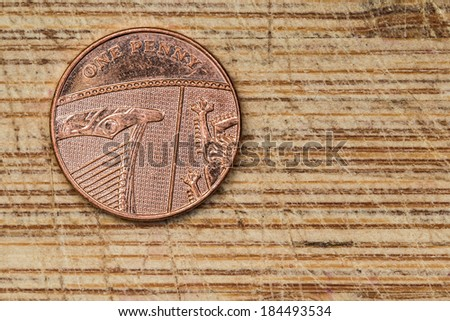 One Penny Coin on a Wood Background