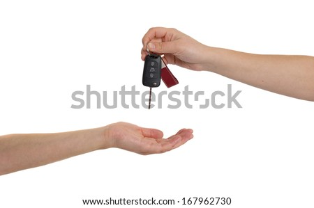 One Person's  hand passing car keys to another person. - stock photo