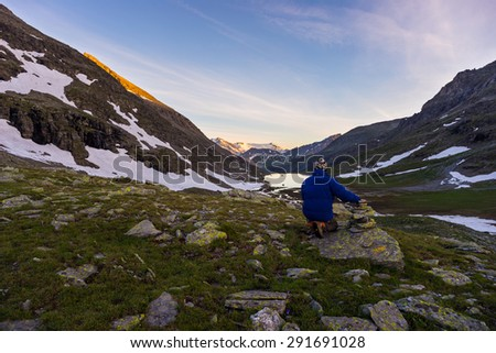 One person sitting on rocky terrain and watching a colorful sunrise high up in the Alps. Wide angle view from above with glowing mountain peaks in the background. Summer adventure and exploration. - stock photo