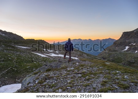One person standing on rocky terrain and watching a colorful sunrise high up in the Alps. Wide angle view from above with glowing mountain peaks in the background. Summer adventure and exploration. - stock photo