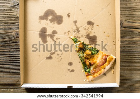 One piece of pizza in cardboard pizza box. Top view - stock photo