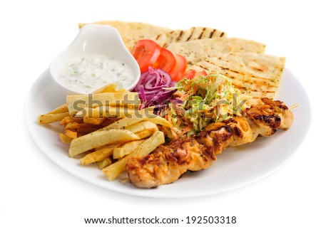 one portion of french fries, chicken kebab, salad and roasted pita - stock photo