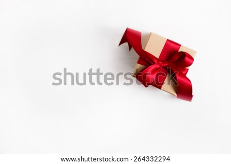 One present with a red ribbon on wooden white background.