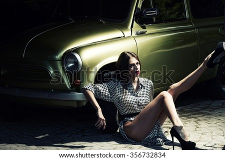One pretty sensual thinking straight slim fashionable young woman with long legs in black high heeled shoes sitting on road near beautiful retro car golden color outdoor sunny day, horizontal picture
