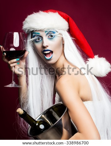 One pretty young fairy new year girl with winter blue makeup long white eyelashes and hair wig in red christmas santa hat with cork bottle in pail and red wine glass on pink studio backdrop, vertical