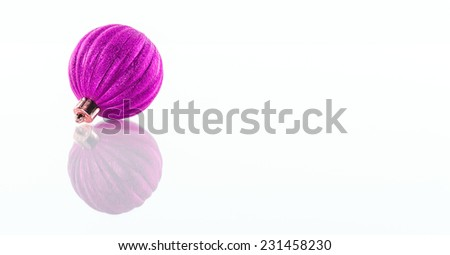 One purple, pink Christmas ball isolated on white reflective perspex background with copy space - stock photo