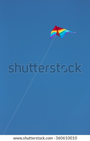 One rainbow colored kite flying high in a blue sky.