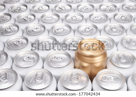 One Raised Gold Can Among a Group of Aluminum Beverage Cans - stock photo