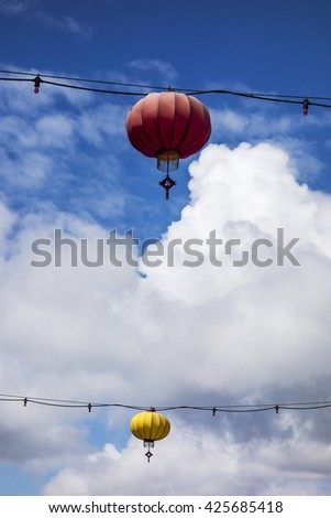 One red and one yellow lantern hang from wires overhanging the main street in the Chinatown district of Victoria, BC. - stock photo