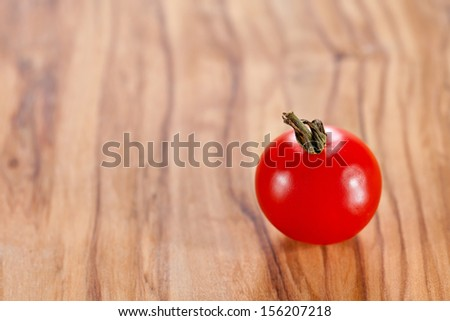 One red cherry tomato on olive oil wood surface
