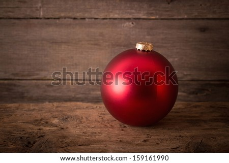 One red christmas ball on the wooden background - stock photo