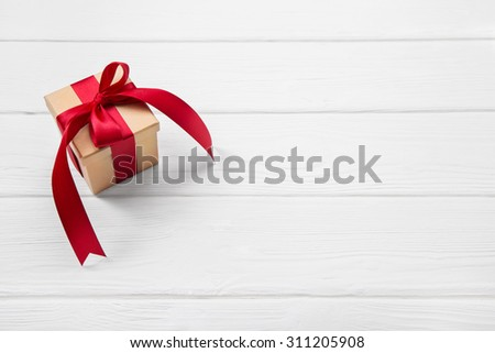 One red christmas present on white wooden background with a big ribbon. - stock photo