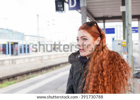 One red headed young female commuter wearing a coat waits with her hands crossed at a station for the train