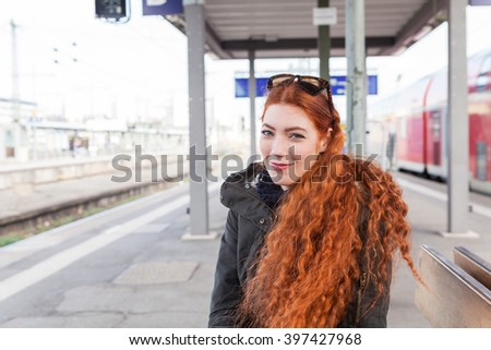 One red headed young female commuter wearing a coat waits with her hands crossed at a station for the train - stock photo
