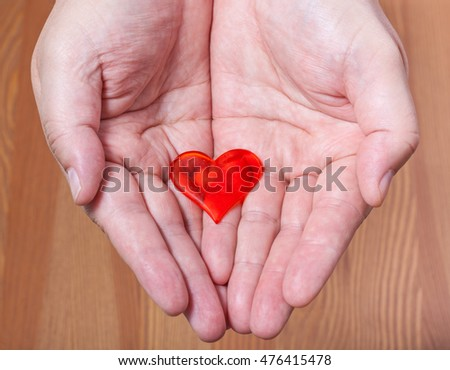 one red heart on male palms with wooden background