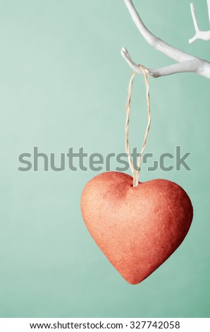 One red heart ornament hanging by string  from bare white branches of artificial tree against turquoise background.   - stock photo