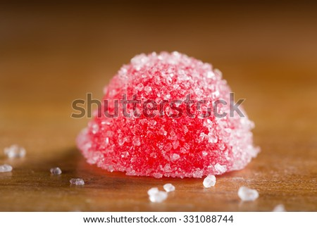 One red jelly candy with white sugar over wooden background - stock photo