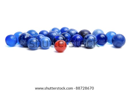 One red marble in group of blue vintage marbles isolated on a white background