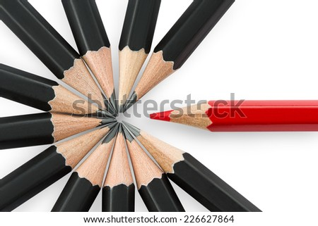 One red pencil standing out from the circle of black pencils - stock photo