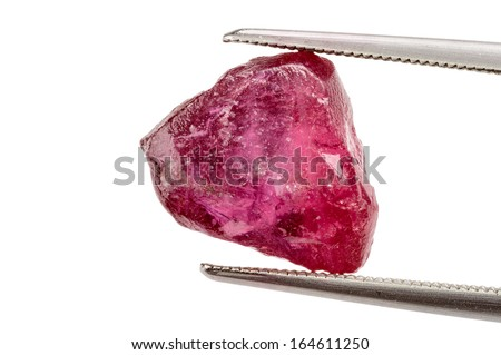 One red ruby crystal held by tweezers - stock photo