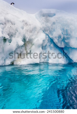 One remaining penguin debates jumping from high iceberg - stock photo