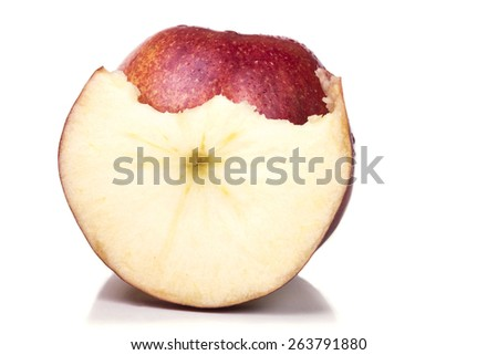 One ripe red apple with a slice bitten - stock photo