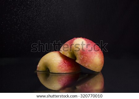 One ripe tasty beautiful seasoning berry fruit of red yellow wet apple cut into two parts with water spray lying in studio on black background, horizontal picture - stock photo