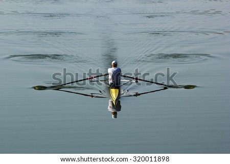 One rower in a boat, rowing on the tranquil river. soft focus. - stock photo