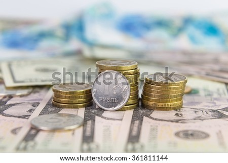 One ruble against the backdrop of stacked coins 10 rubles lying on dollar bills
