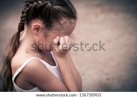 one sad child sitting on the floor and holding her head in her hands