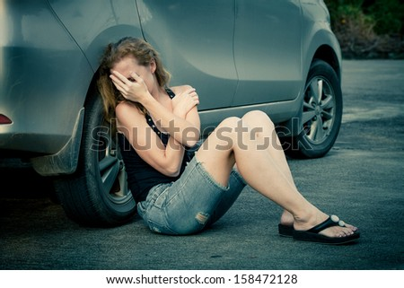 one sad woman sitting on the road near a car - stock photo