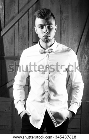One sensual young handsome man with beautiful hairstyle in shirt with bow standing in studio on wooden background black and white, vertical picture - stock photo