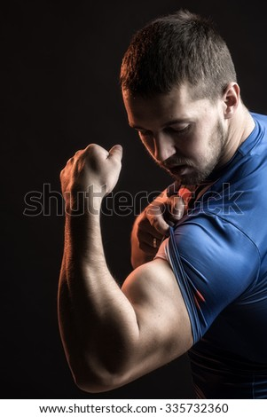 One sexual strong young man with muscular body in blue sport shirt showing big biceps on hand standing on studio black background, vertical picture