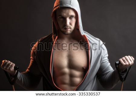One sexual strong young man with muscular body in grey sport jacket with hood holding training device standing on studio black background, horizontal picture